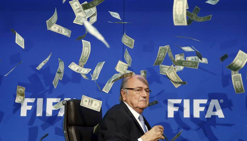 British comedian known as Lee Nelson (unseen) throws banknotes at FIFA President Sepp Blatter as he arrives for a news conference after the Extraordinary FIFA Executive Committee Meeting at the FIFA headquarters in Zurich, Switzerland July 20, 2015. World football's troubled governing body FIFA will vote for a new president, to replace Sepp Blatter, at a special congress to be held on February 26 in Zurich, the organisation said on Monday. REUTERS/Arnd Wiegmann TPX IMAGES OF THE DAY - RTX1L3H3