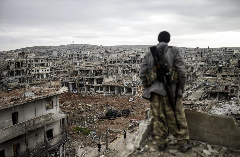 TOPSHOTS Musa, a 25-year-old Kurdish marksman, stands atop a building as he looks at the destroyed Syrian town of Kobane, also known as Ain al-Arab, on January 30, 2015. Kurdish forces recaptured the town on the Turkish frontier on January 26, in a symbolic blow to the jihadists who have seized large swathes of territory in their onslaught across Syria and Iraq. AFP PHOTO/BULENT KILICBULENT KILIC/AFP/Getty Images