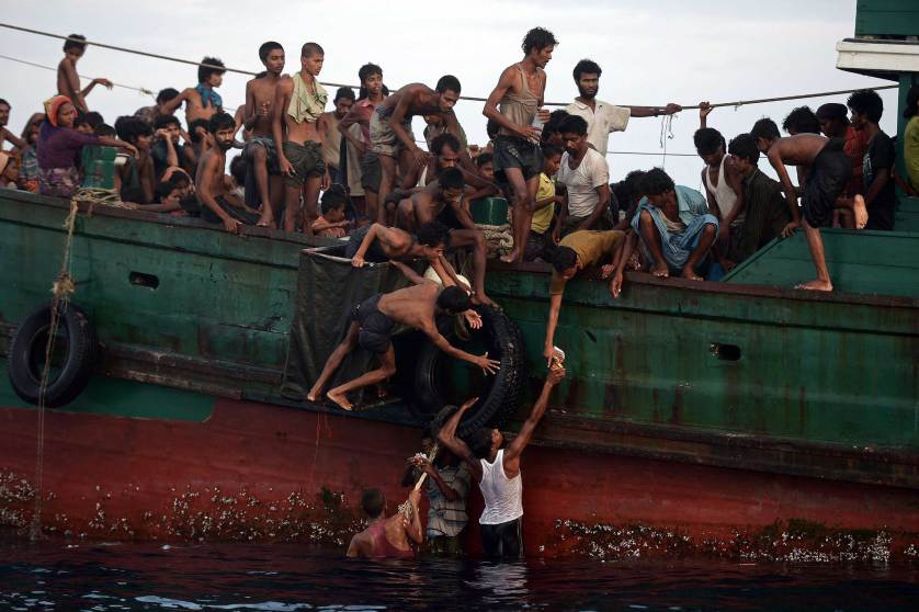 TOPSHOTS Rohingya migrants pass food supplies dropped by a Thai army helicopter to others aboard a boat drifting in Thai waters off the southern island of Koh Lipe in the Andaman sea on May 14, 2015. A boat crammed with scores of Rohingya migrants -- including many young children -- was found drifting in Thai waters on May 14, with passengers saying several people had died over the last few days. AFP PHOTO / Christophe ARCHAMBAULTCHRISTOPHE ARCHAMBAULT/AFP/Getty Images