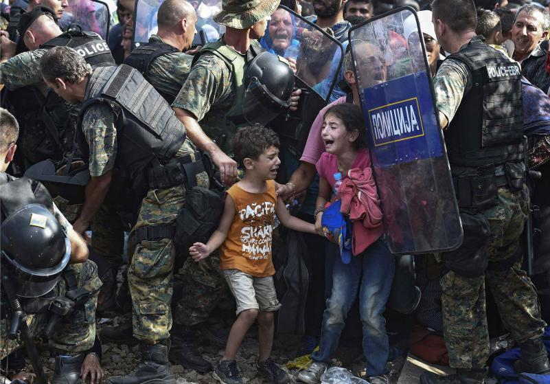epaselect epa04891691 Children cry as migrants waiting on the Greek side of the border break through a cordon of Macedonian special police forces to cross into Macedonia, near the southern city of Gevgelija, The Former Yugoslav Republic of Macedonia, 21 August 2015. Macedonian police clashed with thousands of migrants attempting to break into the country after being stranded in no-man's land overnight, marking an escalation of the European refugee crisis for the Balkan country. EPA/GEORGI LICOVSKI