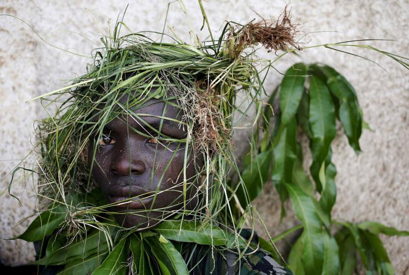 A protester wears grass around his face to obscure his identity during a protest against President Pierre Nkurunziza's decision to run for a third term, in Bujumbura, Burundi, May 11. 2015. East African leaders will hold a summit in Tanzania on May 13 aimed at breaking the political deadlock in Burundi and ensuring the country holds peaceful elections, Tanzania's presidency says. REUTERS/Goran Tomasevic TPX IMAGES OF THE DAY