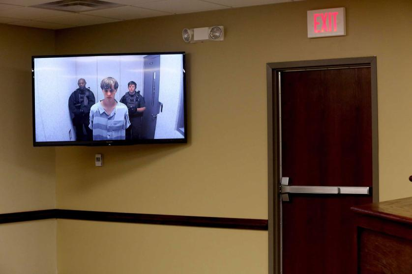 epa04809298 Suspect Dylann Roof (C) appears via video link at a bond hearing in court in North Charleston, South Carolina, USA, 19 June 2015. He is charged with nine counts of murder and firearms charges in the shooting deaths on 17 June at Emanuel African Methodist Episcopal Church in downtown Charleston. EPA/Grace Beahm / POOL