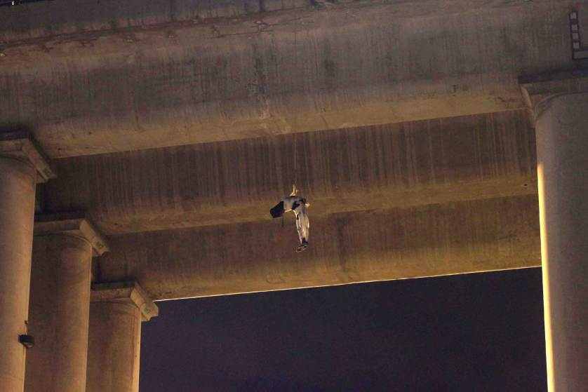 An unidentified dead man hangs from his waist under an overpass in the southern part of Mexico City, early Monday, Oct. 19, 2015. The man was found wrapped in white bandages and a cap, or hoodie, was covering his head. This is the first time a body appears on a bridge or overpass in Mexico City, a common practice among criminal gangs fighting for control of turf in other regions of Mexico. Mexico City authorities have repeatedly stated that the capital is safe from the wave of violence that continues to affect many parts of the country. (AP Photo/Jair Cabrera)