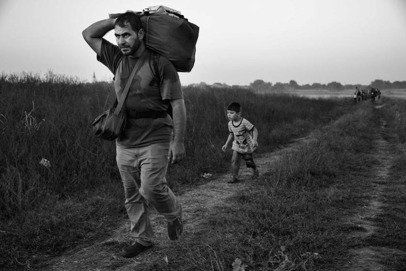 A man walks with his son behind him as they make their way to the train station in Tovarnik, Croatia, on the border with Serbia. In the Balkans, many migrants began traveling by foot, echoing more ancient journeys, September 17, 2015 James Nachtwey for TIME