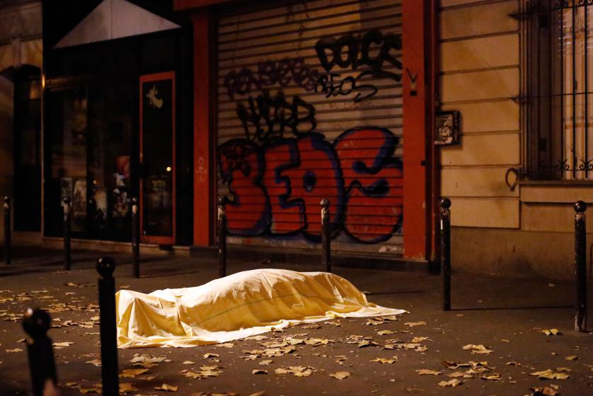 A victim under a blanket lays dead outside the Bataclan theater in Paris, Friday Nov. 13, 2015. Well over 100 people were killed in a series of shooting and explosions explosions. French President Francois Hollande declared a state of emergency and announced that he was closing the country's borders. (AP Photo/Jerome Delay)