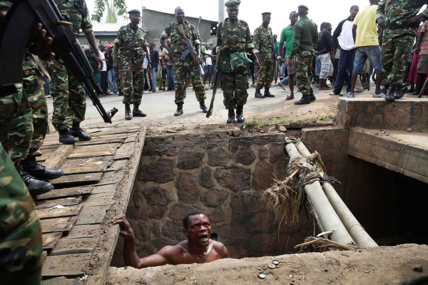 Jean Claude Niyonzima, a suspected member of the ruling party's Imbonerakure youth militia, pleads with soldiers to protect him from a mob of demonstrators after he emerged from hiding in a sewer in the Cibitoke district of Bujumbura, Burundi, Thursday May 7, 2015. Niyonzima fled from his house into a sewer under a hail of stones thrown by a mob protesting against President Pierre Nkurunziza's decision to seek a third term in office. At least one protestor has died in clashes with the widely feared Imbonerakure militias and police, sending scores to the streets seeking revenge. Jean Claude Niyonzima managed to flee from his house under a hail of stones into a covered sewer, where he remained till the army fired shots into the air to disperse the crowd.(AP Photo/Jerome Delay)