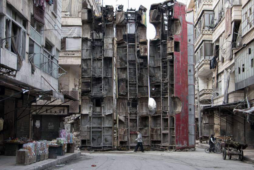 A young boy walks past a makeshift barricade made of wreckages of buses to obstruct the view of regime snipers and to keep people safe, on March 14, 2015 in the rebel-held side of the northern Syrian city of Aleppo. Syria's conflict enters its fifth year on March 15, 2015 with the regime emboldened by shifting international attention and a growing humanitarian crisis exacerbated by the rise of the Islamic State group. AFP PHOTO / KARAM AL-MASRIKARAM AL-MASRI/AFP/Getty Images