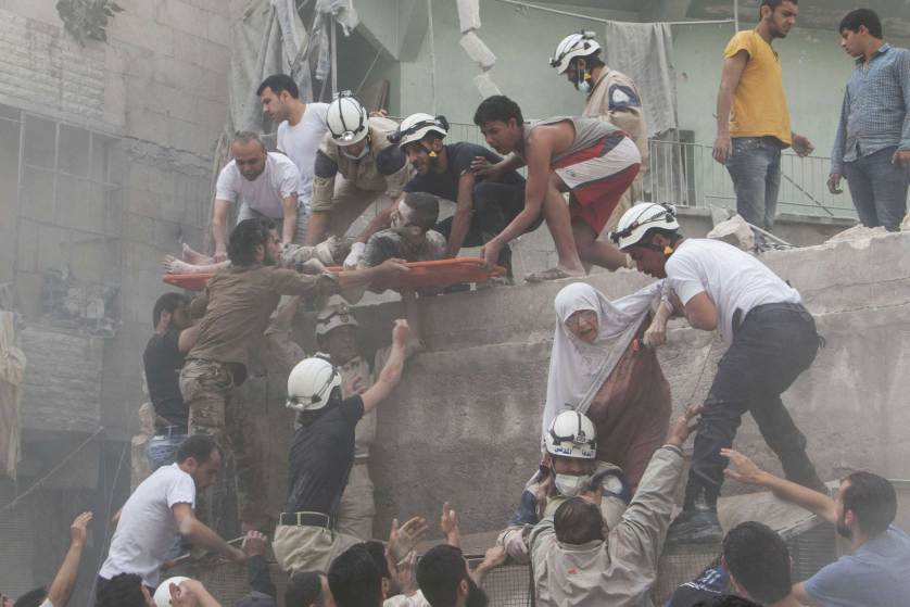 TOPSHOTS Syrian rescue workers and citizens evacuate people from a building following a reported barrel bomb attack by Syrian government forces on the central al-Fardous rebel held neighbourhood of the northern Syrian city of Aleppo, on June 9, 2015. AFP PHOTO / KARAM AL-MASRI KARAM AL-MASRI/AFP/Getty Images