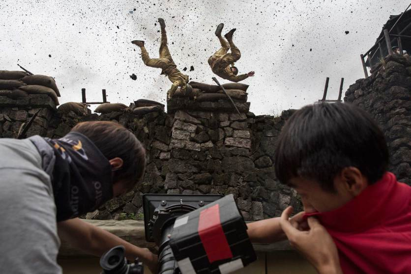 "FANGYAN, CHINA - AUGUST 13: (CHINA OUT) Chinese actors playing Japanese soldiers are blown off a wall in an explosion during the filming of the series ""The Last Noble,"" set during the second Sino-Japanese War on August 13, 2015 in Fangyan, China. Seventy years after the end of World War II, there is still widespread resentment across China toward Japan and its wartime misdeeds. It is estimated that hundreds of films depicting China's victory over Japan in 1945 are produced on the mainland every year and the genre remains one of the country's most popular entertainment draws. The conflict and what critics say is a refusal by most Japanese leaders to fully apologize for history, has long set the tone for strained relations between the two countries and and at times fuelled regional tension. Many of the films are shot in and around Hengdian Studios, Asia's largest production facility. (Photo by Kevin Frayer/Getty Images)"