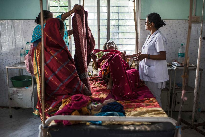 Nazreen Khatoon winces in pain as she is repositioned by a nurse as she lies gravely ill while suffering from severe postpartum anemia at the Tezpur Civil Hospital in Tezpur, Assam, India, April 2015. Khatoon delivered her son, Kashari Pam, roughly three weeks prior, and returned to the hospital about two weeks after delivery when her condition worsened. When we met her, she was in dire need of both blood and iron, and was not receiving either from the Tezpur Hospital; she was eventually referred to a private hospital, where she was able to receive better care, but at a great expense to the family. Many of Assam's state-run medical facilities are often overcrowded and unhygenic, with an insufficient number of doctors, and patients sprawled out in the floors and hallways due to a limited number of beds. Assam has the highest rate of women dying in chidbirth and from pregnancy-related causes in all of india, where roughly 50,000 women die annually in childbirth across the country. Many families in Assam work on the tea plantations, where there is a high rate of pregnant and lactating women who are severely anemic due to poor diets and little to no prenatal care, leading to a high number of pregnancy complications. (Credit: Lynsey Addario/ Getty Images reportage for Every Mother Counts)