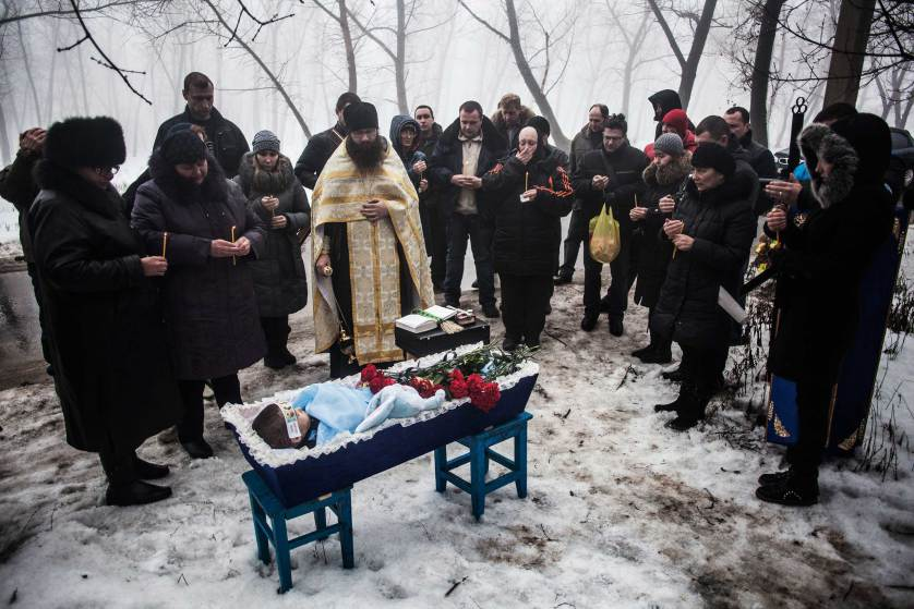Mourners gather around a coffin bearing Artiam, 4, who was killed in a Ukrainian army artillery strike, during his funeral in Kuivisevsky district on the outskirts of Donetsk, eastern Ukraine, Tuesday, Jan. 20, 2015. At least three civilians were killed in shelling Tuesday in eastern Ukraine as fighting continued between government and rebel forces in the separatist-held city of Donetsk. (AP Photo/Manu Brabo)