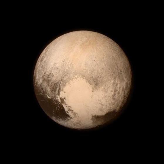 "13 Jul 2015 --- Pluto nearly fills the frame in this image from the Long Range Reconnaissance Imager (LORRI) aboard NASA's New Horizons spacecraft, taken on July 13, 2015 when the spacecraft was 476,000 miles (768,000 kilometers) from the surface. This is the last and most detailed image sent to Earth before the spacecraft's closest approach to Pluto on July 14. The color image has been combined with lower-resolution color information from the Ralph instrument that was acquired earlier on July 13. This view is dominated by the large, bright feature informally named the ""heart,"" which measures approximately 1,000 miles (1,600 kilometers) across. The heart borders darker equatorial terrains, and the mottled terrain to its east (right) are complex. However, even at this resolution, much of the heart's interior appears remarkably featurelessópossibly a sign of ongoing geologic proce --- Image by © NASA/APL/SwRI/Corbis"