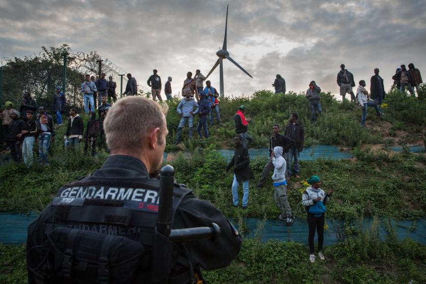 CALAIS, FRANCE - JULY 30: Gendarmerie attempt to prevent people from entering the Eurotunnel terminal in Coquelles on July 30, 2015 in Calais, France. Hundreds of migrants are continuing to attempt to enter the Channel Tunnel and onto trains heading to the United Kingdom. (Photo by Rob Stothard/Getty Images) ***BESTPIX***
