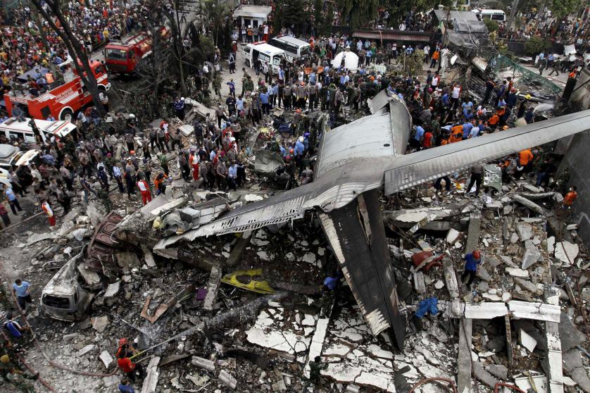 Security forces and rescue teams examine the wreckage of an Indonesian military C-130 Hercules transport plane after it crashed into a residential area in the North Sumatra city of Medan, Indonesia, June 30, 2015. At least 30 people were killed when the military transport plane crashed into a residential area two minutes after take-off in northern Indonesia on Tuesday, putting a fresh spotlight on the country's woeful air safety record. REUTERS/Roni Bintang TPX IMAGES OF THE DAY