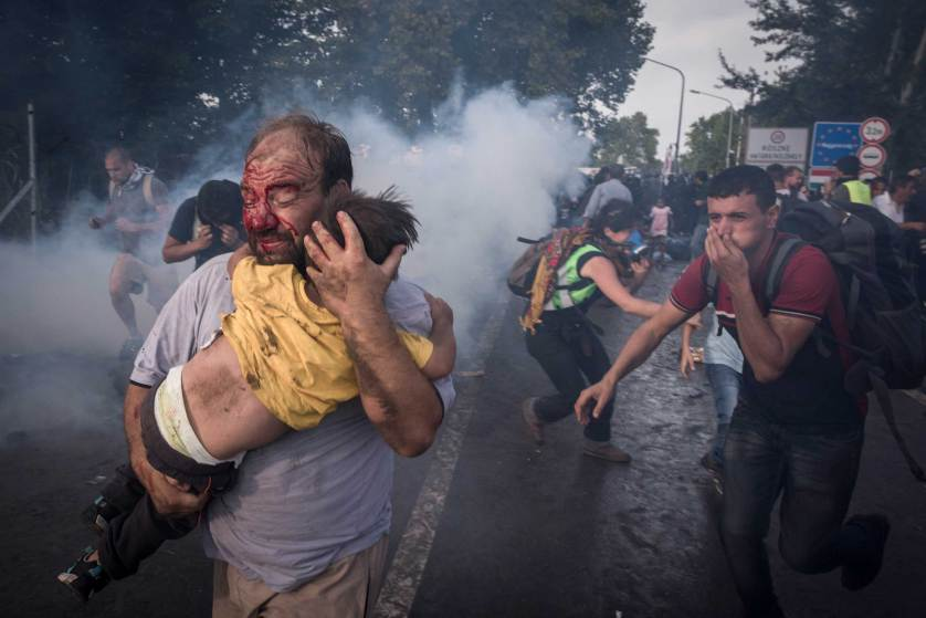 A migrant holds his child during a clash with Hungarian riot police at the Horgos border crossing in Serbia, Sept. 16, 2015. Hundreds of migrants remained stranded on Serbia?s border with Hungary early Wednesday as Hungary?s decision to seal its border rippled across Europe and other migrants scrambled to find alternative routes, in an effort, in most cases, to reach Germany. (Sergey Ponomarev/The New York Times)