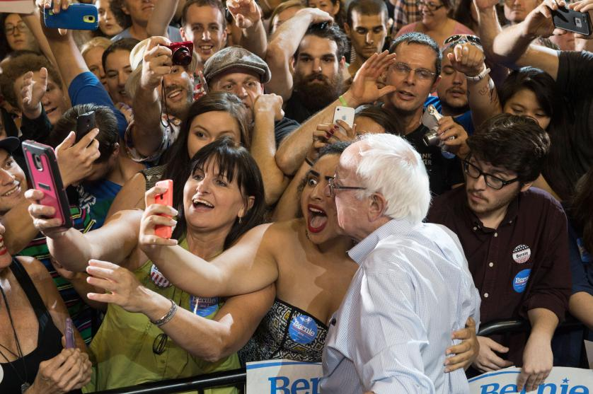 Naomi Scott, center, of McMinnville, Ore., takes a picture with Democratic presidential candidate Sen. Bernie Sanders, I-Vt., at a rally, Sunday, Aug. 9, 2015, at the Moda Center in Portland, Ore. (AP Photo/Troy Wayrynen)
